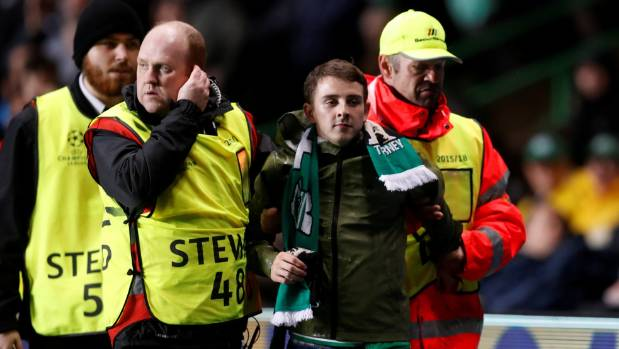 A Celtic fan is removed by stewards after invading the pitch.