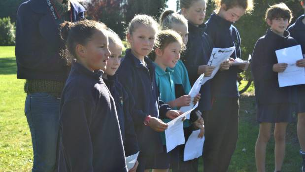 Springlands School pupils welcome people to the unveiling of the latest poem to join the Taylor River Writers' Walk.