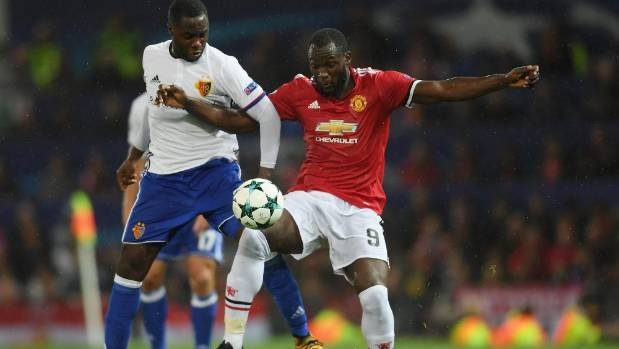 Eder Balanta of FC Basel and Romelu Lukaku (right) of Manchester United battle for possession at Old Trafford.