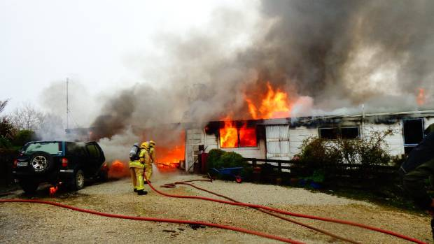 Firefighters work to gain control of the flames engulfing a Waitomo home.