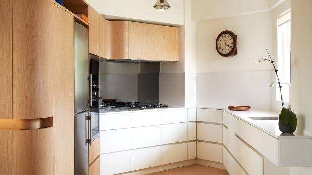 The kitchen is positioned on the right side of the central cabinetry. The use of timber veneer on this unit maintains a ...