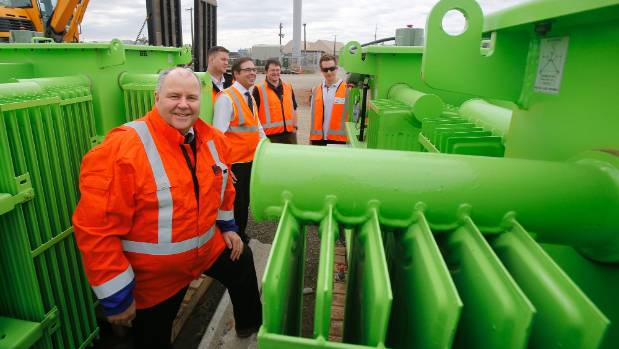 Alpine Energy chief executive Andrew Tombs, front, poses with the new vegetable-oil transformers, with representatives ...