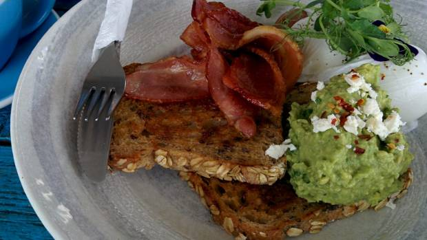 Poached Eggs and feta on avocado with bacon on the side at The Artisan in Wiri, Auckland.