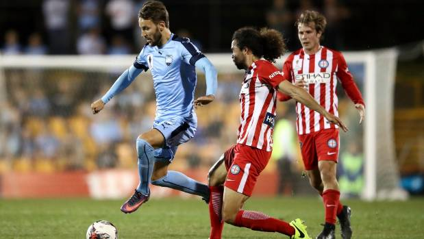 Milos Ninkovic of Sydney FC dribbles the ball past Melbourne City defenders during their FFA Cup quarterfinal.