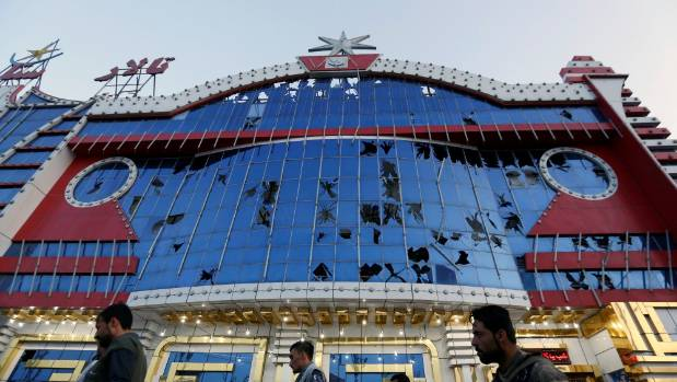 People survey the damage of a building with broken windows after a suicide attack near the national cricket stadium in ...