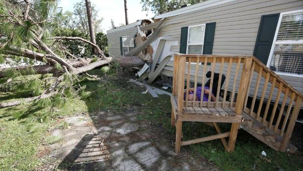 A resident of a mobile home park lies near a home that was destroyed by a falling tree in the wake of Hurricane Irma in ...