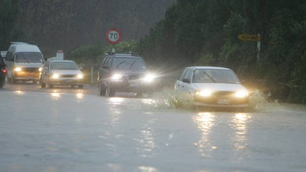 Cars drive through floods in 2006 at Ruby Bay.