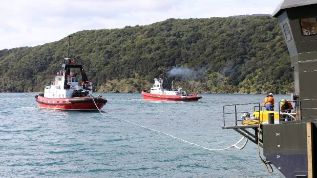 A tug boat prepares to tow the barge off the airbags to its berth.