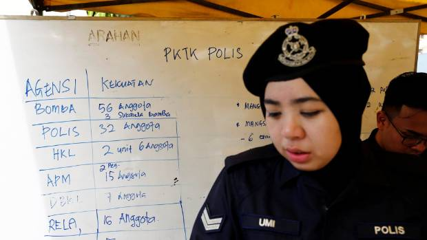 A policewoman stands next to a noticeboard accounting for manpower involved in the aftermath of a fire at religious ...