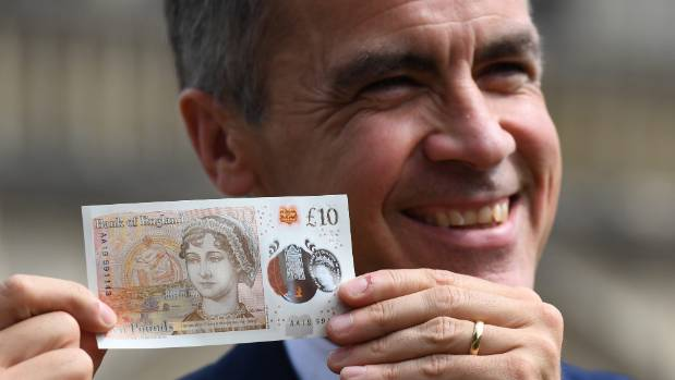 Bank of England Governor Mark Carney poses with one of the central bank's new £10 notes, featuring British author Jane ...