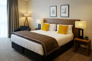 The bedroom is decked out in modern colours in the Executive Suite at The Victoria Hotel in Dunedin.