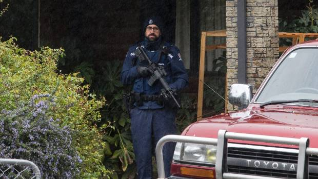 An armed police officer guards a house near Hanmer Springs after shots were fired and a man was kidnapped on Monday night.