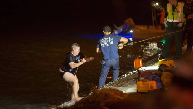 Emergency staff emerge from the water after searching for the car.