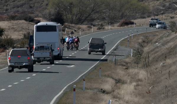 Ute overtakes bus and cyclists near Lake Pukaki during the Twizel to Timaru cycle race.