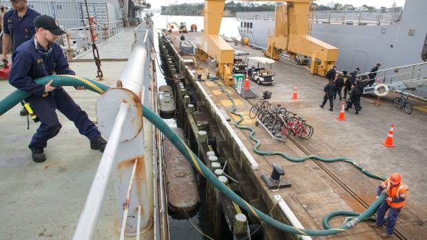 Chritian Raynor removes the pipes from HMNZS Endeavour once fuel is pumped from the ship.