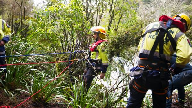 Firefighters abseil down the riverbank to rescue Mack.