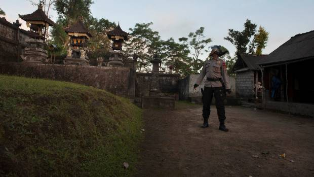 A police officer searches for residents who did not evacuate an area close to the summit of Mount Agung.