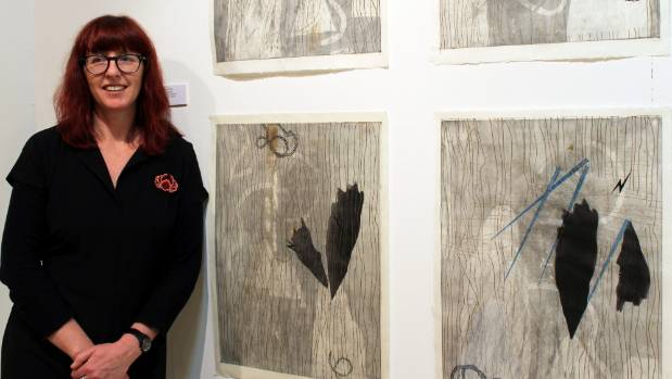 Michaela Stoneman beside her Wai Wairua Series prints at the opening of her exhibition 'The Nun and the Poet: Jerusalem' ...
