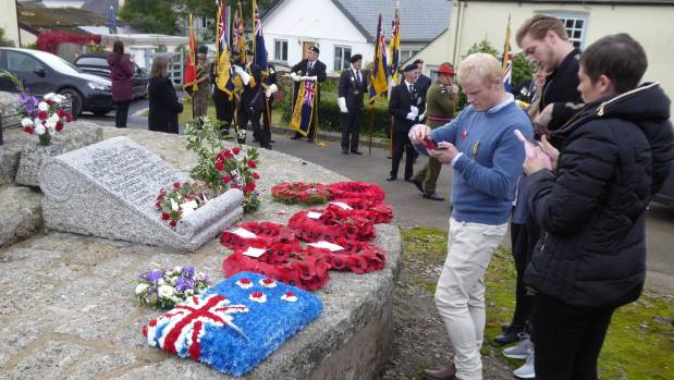 Visitors look at the wreaths laid in remembrance.
