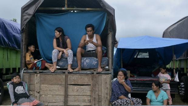 Villagers who live near the volcanic Mt Agung sit inside a truck as a temporary shelter on the resort island of Bali.