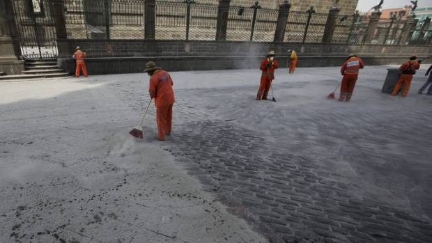 Municipal workers sweep a floor covered with ash after an early eruption of Popocatepetl volcano in Puebla, Mexico.