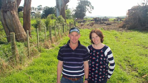 Recent-planted natives grow alongside some mature trees while the clearing continues behind Nathan and Kate Williams on ...