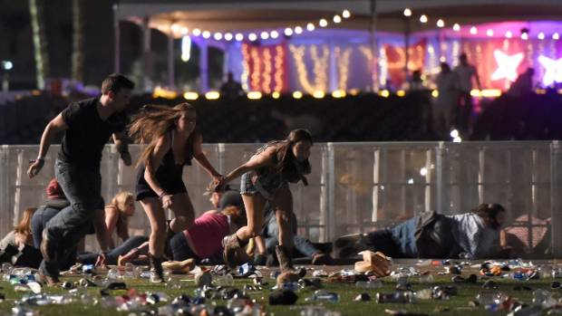 Concert-goers flee after a hail of gunshots rained down on them from the 32nd floor of a Las Vegas hotel