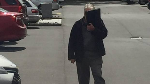 Martin Lawes covered his face as he left the North Shore District Court.