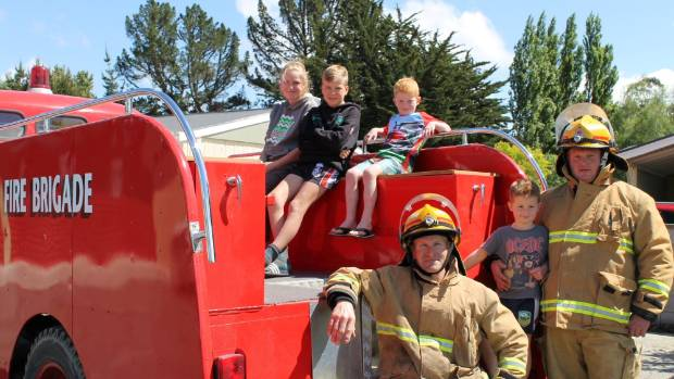 Children, from left, Emma Merchant, Jack Merchant, Liam Eaton and Riley Eaton on the back of the vintage fire engine ...
