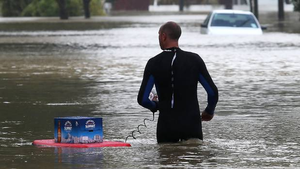 A Riverlaw Tce resident floats the essentials on a bodyboard during the 2014 floods.