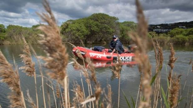 Police in an inflatable dinghy search the Paincalak Creek, in Victoria.