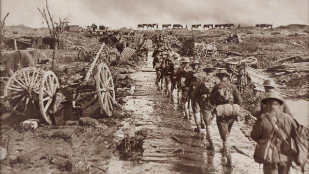 A line of infantry marching along a muddy corduroy track strewn with debris