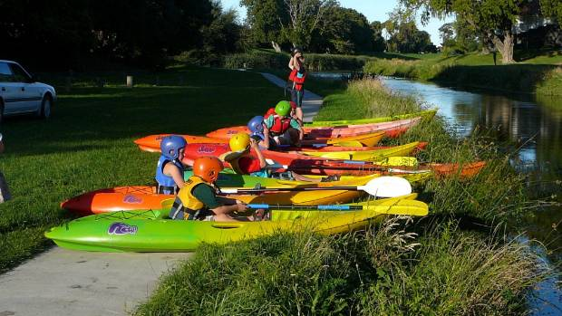 Lined up on the river's edge, ready to try out their canoes.