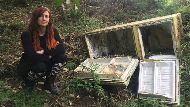 Diana Warnes sits beside an old fridge dumped down a bank and into the bush in Gordons Rd, Rocky Bay.