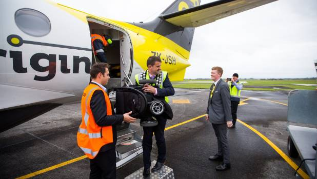 New Plymouth mayor Neil Holdom, centre, with Originair charters manager Gary Jeffcott, right, helps unload bags from the ...