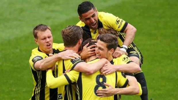 Wellington Phoenix's Ali Abbas jumps on his team-mates to celebrate a goal on Sunday.
