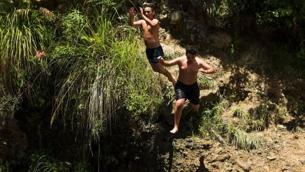 Taipara Hurinui, 14, and Tahaafe Kilisimasi, 13, leap into inviting waters at Horseshoe Bend.