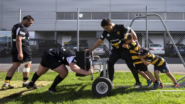 JD Lea, 8, and  Tuni Lea, 7, threw their support behind Mike Kainga on the scrum machine as Reuben O'Neil hit it.