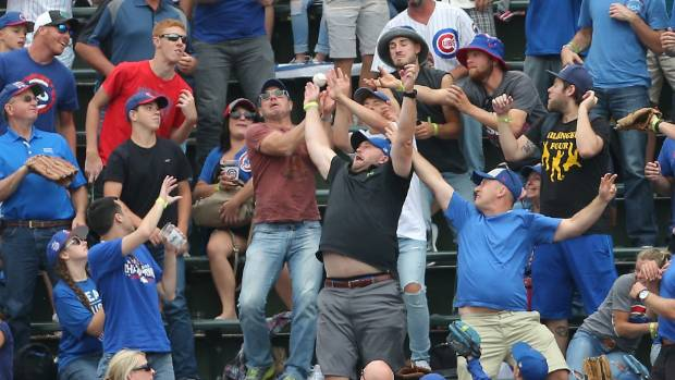 Fans fight for the home run ball off the bat of Atlanta Braves first baseman Freddie Freeman at Wrigley Field.