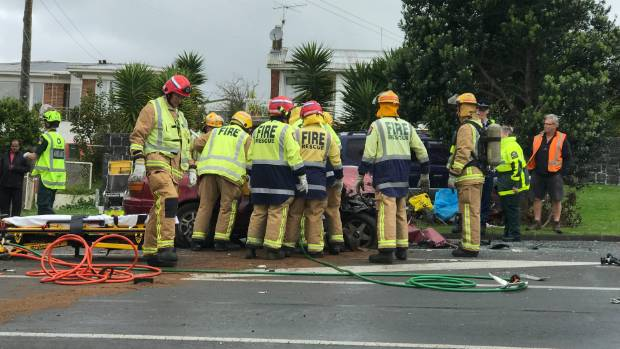 Crews work to free the driver of a red vehicle after a collision with a truck on Massey Rd, Māngere.
