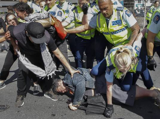 A policewoman kneels on a protester.