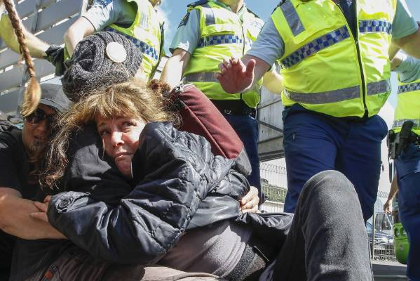 A woman tries to avoid being dragged away by police outside a defence forum being held at Wellington's Westpac Stadium ...