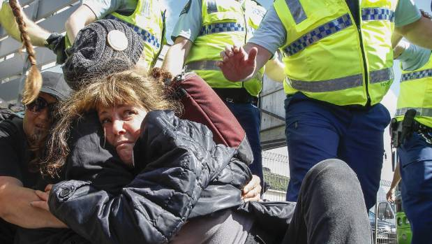 A woman tries to avoid being dragged away by police at Tuesday's protest outside Westpac Stadium in Wellington.