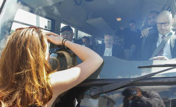 A protester appeals to delegates on a bus attempting to enter the stadium for the defence forum, which was dubbed a ...