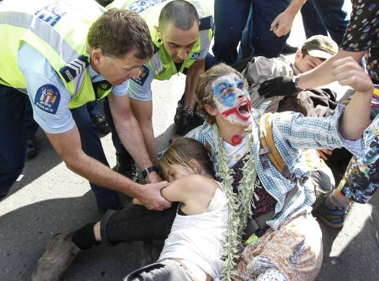 Police remove protesters who locked arms to prevent buses entering Westpac Stadium for the defence forum, which was ...