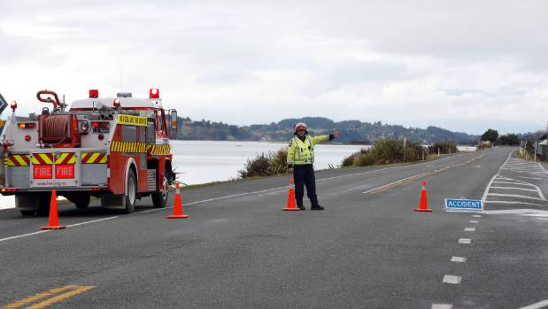 A volunteer firefighter directs traffic at the scene of the crash that killed Zoe Bishop.