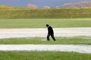 A farmer wades through a flooded paddock in Manawatū.