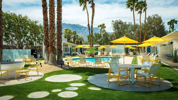 Bright furniture, sun umbrellas and towering palms at classic Palm Springs hotel The Monkey Tree.