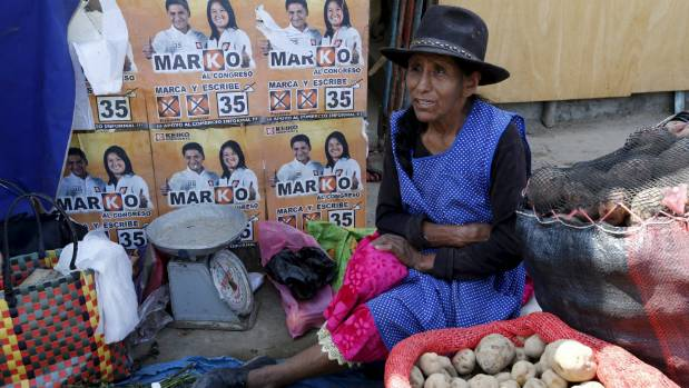 A woman in Lima sells potatoes next to electoral signs of Peru's presidential candidates.