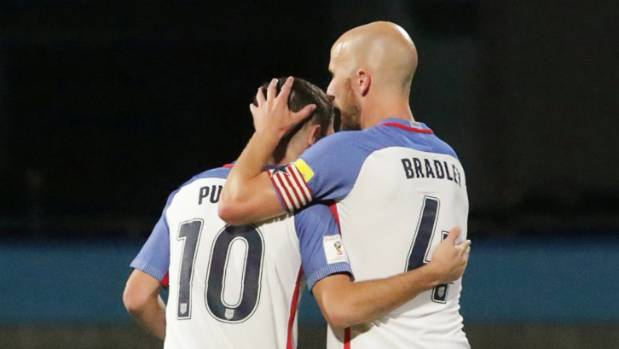 United States players Christian Pulisic and Michael Bradley console each other after their shock loss in Trinidad.